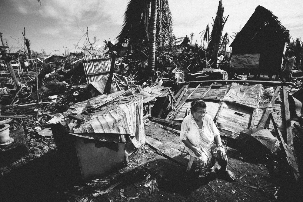 Village of Dulag. An elderly woman sitting in what used to be her living room. Tears are running down her face as she worries for her future and declining health.