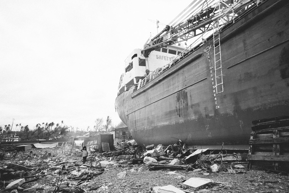 Tacloban City. A girl playing in the rubble next to a gigantic cargo ship washed ashore by the storm surge. Under the ship bodies are buried, but locals are unable to dig them out without big machines.