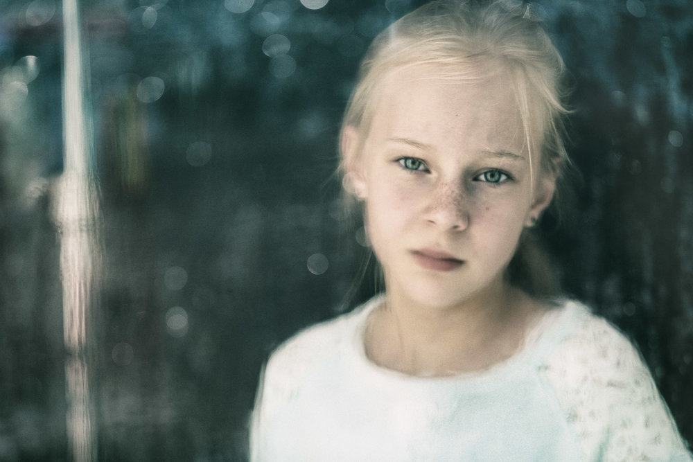Frederikssund, Denmark.  In one of the lowest points of Denmark, Regitze was surrounded by water on all sides of her house as the close-by Roskilde fjord flooded her neighbourhood in a storm. Editorial portrait for Red Cross magazine on children hit by natural disasters.