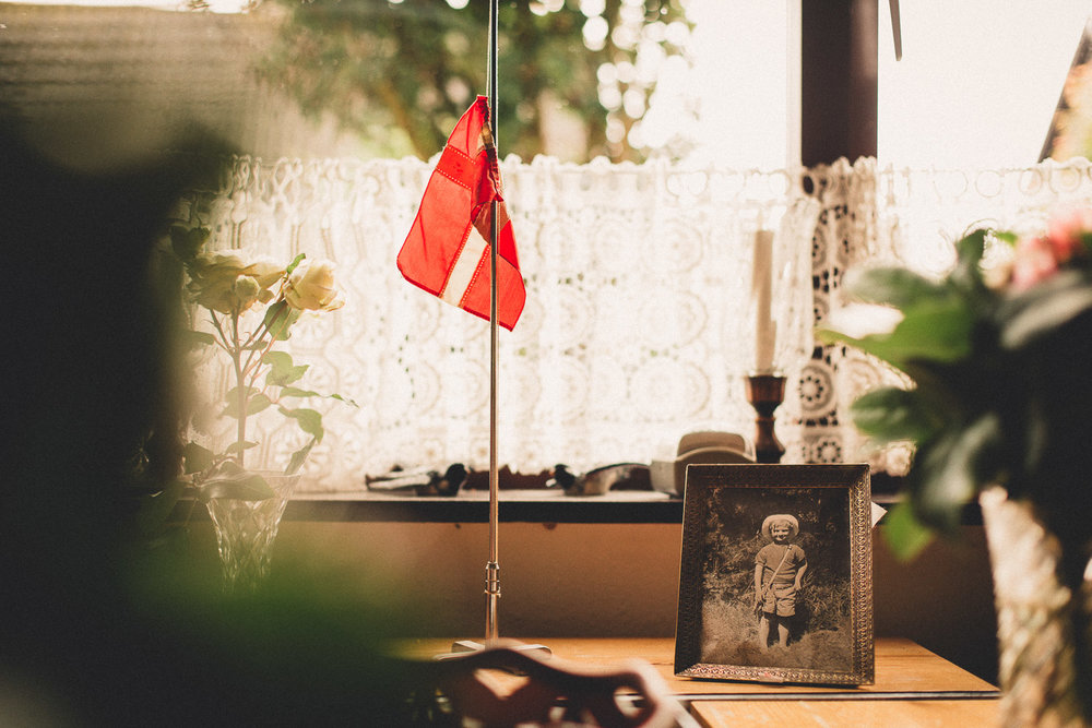A photo of Mikael as a boy stands on the dining table next to a flag on half mast. It is a quiet reminder to the family as they gather in Mikael's house before heading to the chapel for a last goodbye.