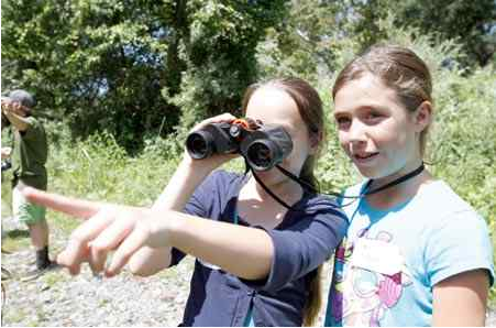 Alyssa Merrill borrows Bryn Melton's binoculars to point out some nesting swallows underneath the bridge at Five-Mile Recreation Area in Chico on Wednesday. The students from Shasta School were participating in one of the nature activities put on by Kids and Creeks, an outdoor educational program. (Frank Rebelo/Staff Photo)