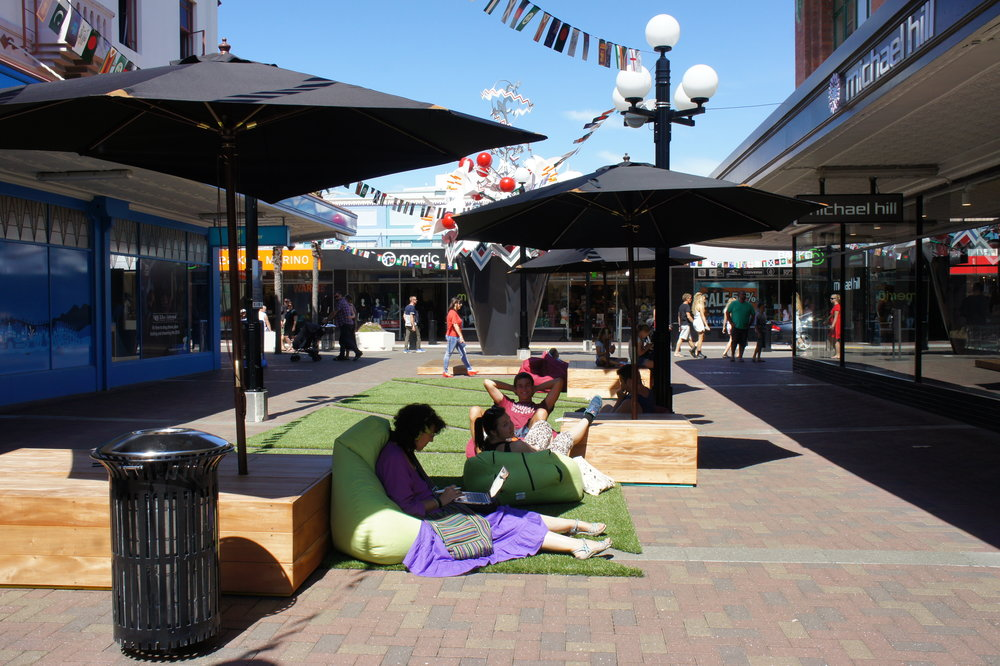 Napier's first MVP   Napier's first 'urban oasis' March 2015 - a pop-up space on Market St had the following features (from near to far): box seating, market umbrellas, bean bags, artificial turf, and a small buskers stage. The judgement call on quality impacted on the quality of materials used to finish the seating boxes and the design of the turf - an Art Deco pattern to match one of Napier's heritage characteristics.  Through the learning loop, Napier Council found that the buskers stage was not being used as buskers preferred performing next to the flow of people along the footpath on Emerson St rather than performing at the urban oasis where people hung-out. The stage was removed in iterations of the oasis, and bistro style seating was tested in the same location.