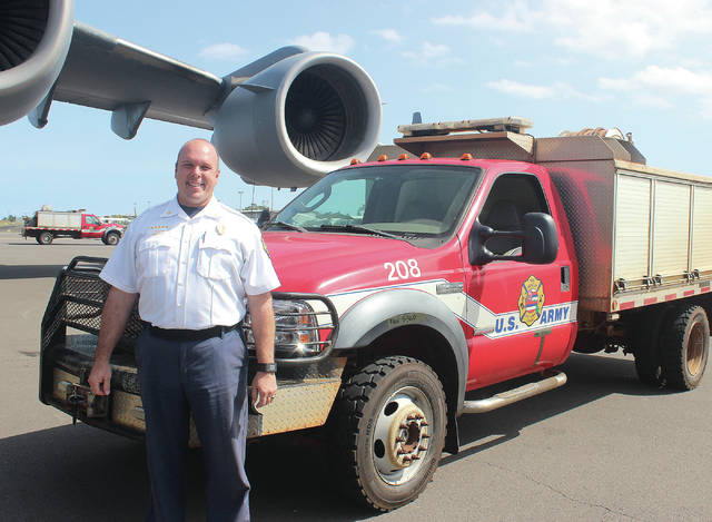 Chief Moller with one of the two brush trucks for PTA that were transported via a C-17 from Oahu to Ellison Onizuka International Airport at Keahole in March 2018. Photo: Chelsea Jensen - West Hawaii Today.