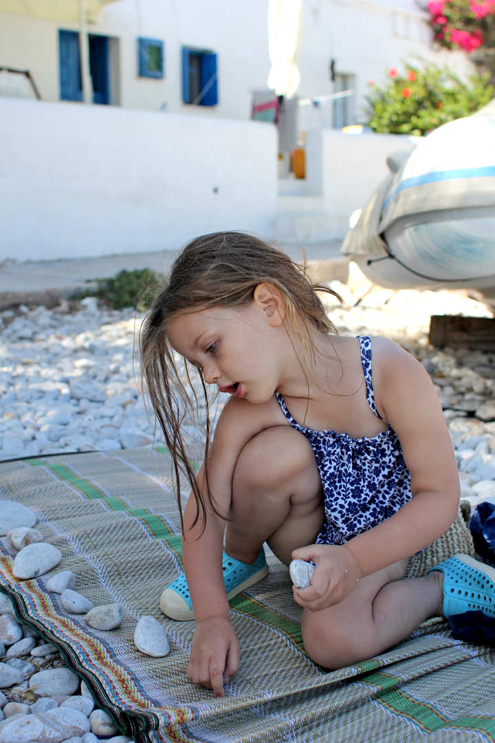 The wind on Folegandros has been crazy, and Alice helps us collect rocks to secure our blankets and mats.