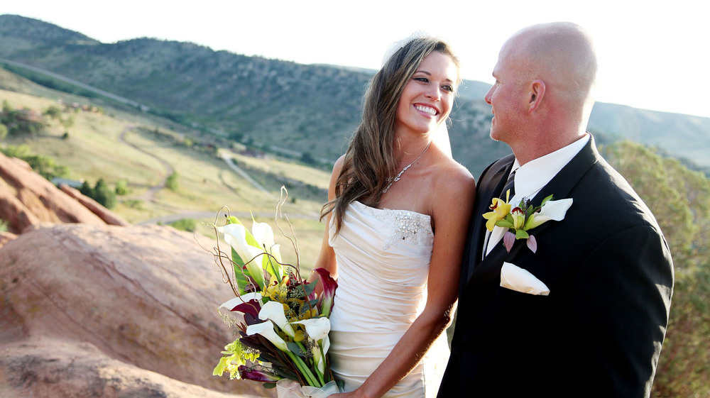 Bride and groom on mountain at wedding.
