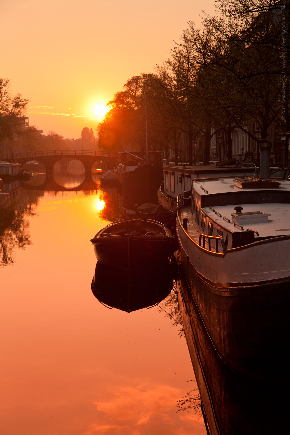 Quiet Canal |Amsterdam, Netherlands April 2014 The sun risesover one of the many canals in Amsterdam. At this early hour the city is usually calm and quiet, with a few bicycle bells the only noise breaking the silence. Purchase printshere