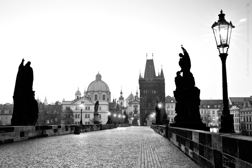 Charles Bridge |Prague, Chezc Republic April 2014 Silhouetted statues line the ancient bridge that connects the two land areas of Prague. Tourists and hawkers alike swarm to this bridge making it impossible to photograph after the early hours of the morning. Purchase printshere