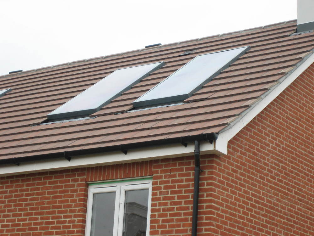 Solar air collectors mounted flush with concrete roof tiles - Woking.JPG