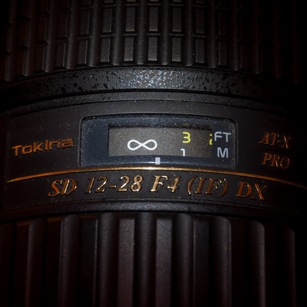 "My Tokina 12-28 focused at approximately 5 feet away at 12mm. If I really want to get the foreground and background in a small bathroom in perfect focus, I can manually dial in the notch to the right edge of the infinity mark. However, I find that simply leaving the focus at the 10 foot ""sweet spot"" (pictured above left) does just fine for real estate photos."
