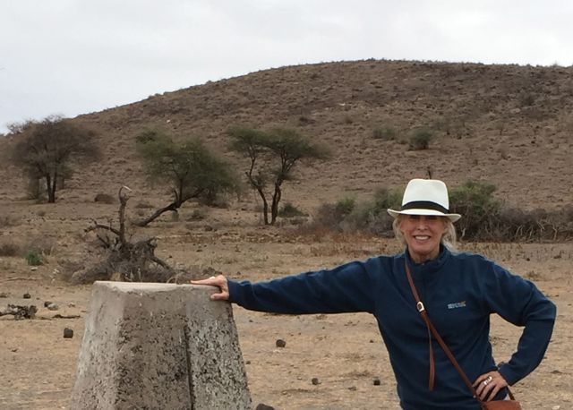 I'm standing at a border marker between Tanzania and Kenya on the first day of photo safari through northern Tanzania.