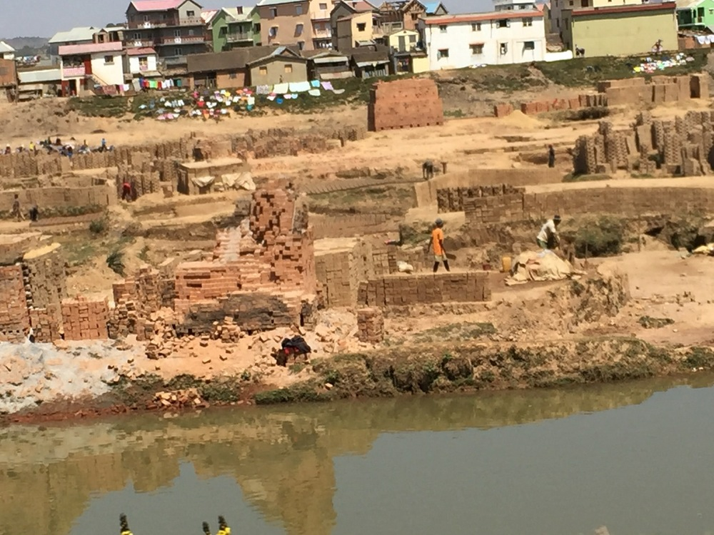 Clay for brick making is extracted from the river bed along the road to Antananarivo. The bricks are fired in kilns on site, fueled by wood burning.