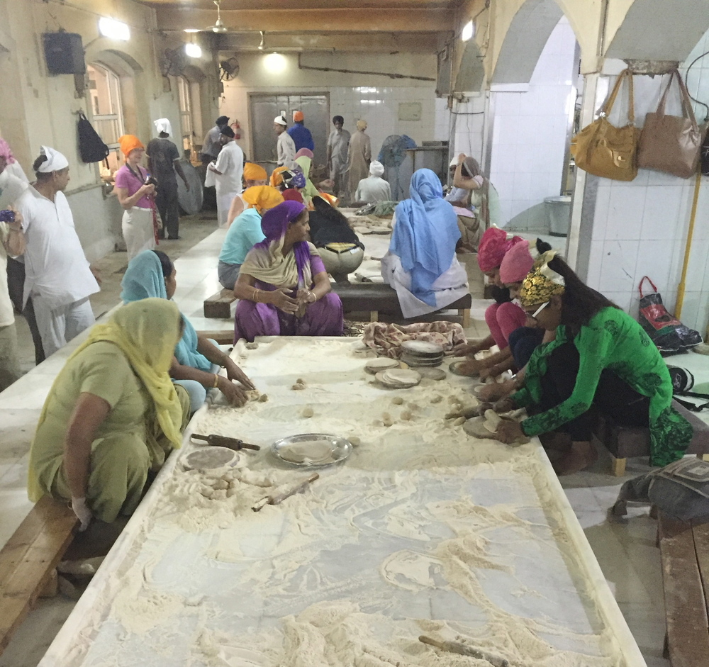 Volunteers knead dough for the countless chapatis served here every day.
