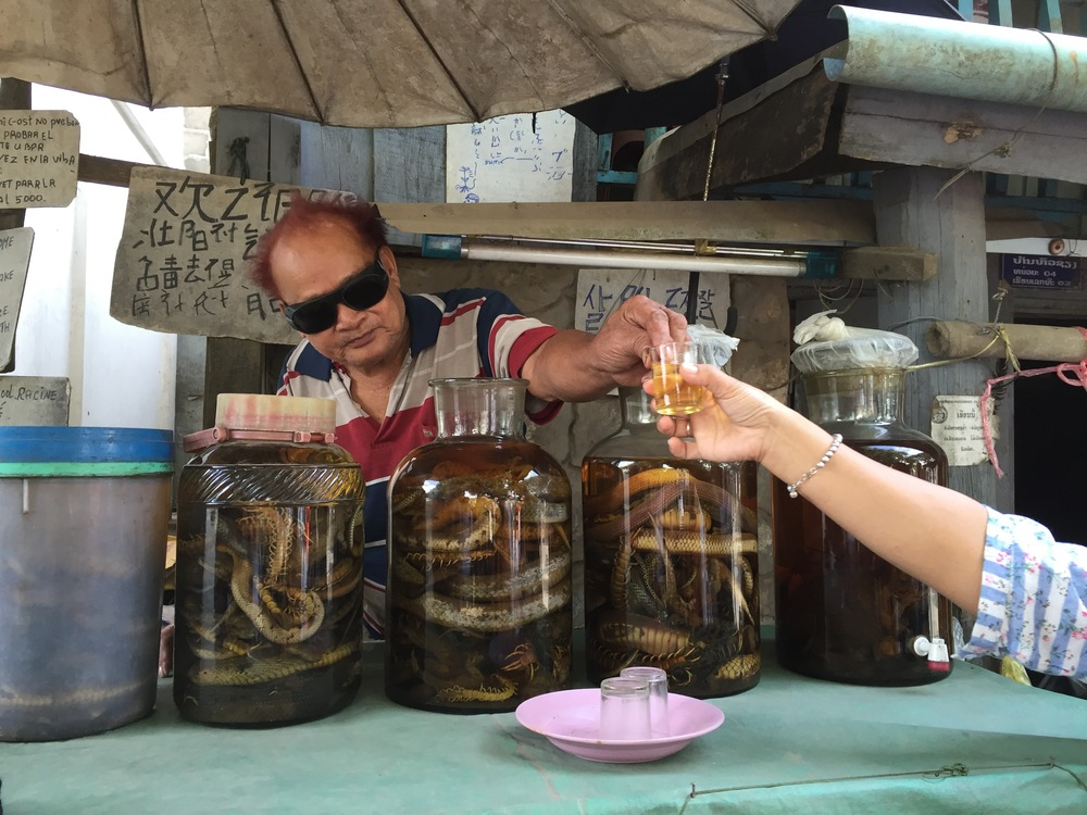 Scorpions, snakes, spiders, and cockroaches are all part of the mix in this locally brewed whiskey...notice the outreached hands seeking to imbibe (not mine!)