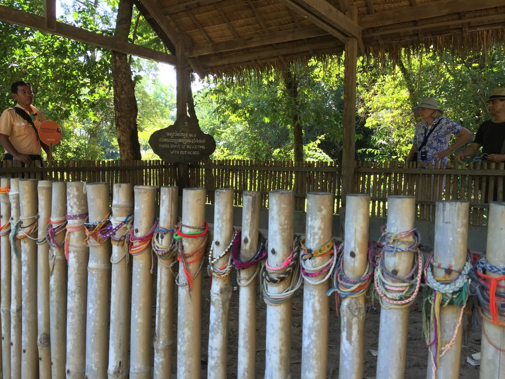 Four-foot bamboo pole fences surround the execution sites of the Killing Fields. Over the years, visitors have draped countless Buddhist prayer bracelets on the fences as tribute to those who died here.