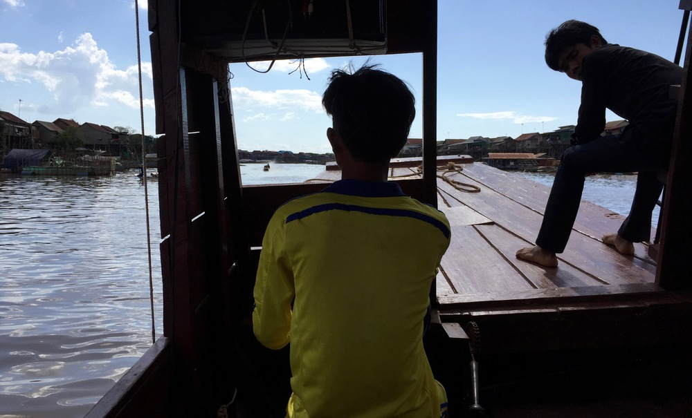 Two young boys from the floating villages of Tonle Sap at the helm of our river boat.