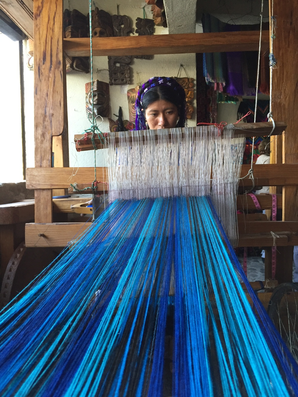 A woman in the textile cooperative in the village of San Antonio Palopo demonstrating Mayan weaving on a traditional loom.