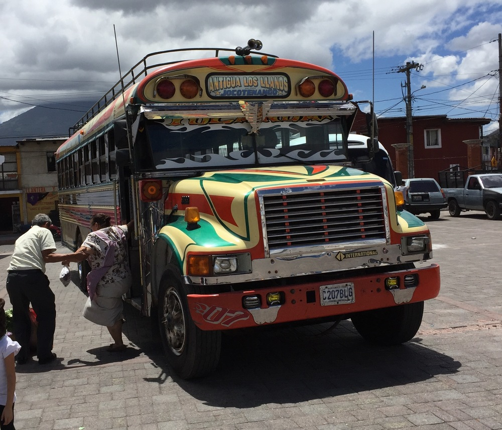 "A ""chicken bus,"" which is basically a souped-up, hot-rod update of an old,  recycled American school bus. We're told these buses are refitted with Caterpillar engines and manual transmissions, and their garrish paint jobs & chrome trim rival any low-rider car. chicken buses are the main mode of transportation in Guatemala."