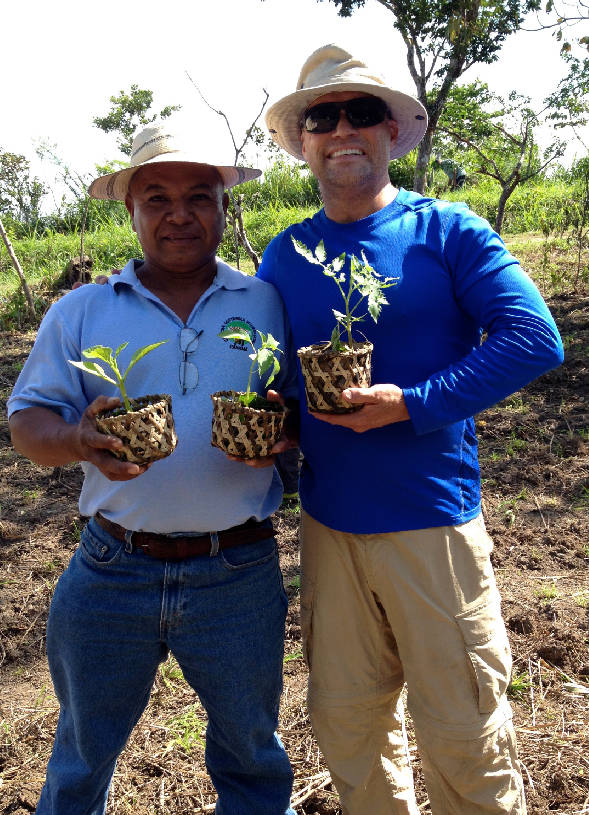 Trip Harris, traveler, poses with our field trainer in Panama with fresh seedlings