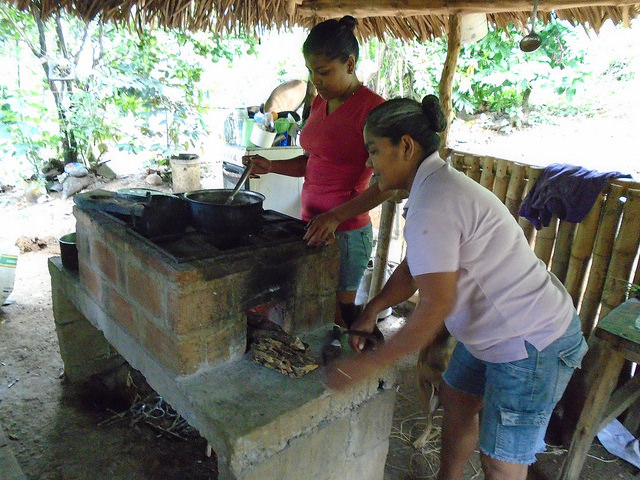 Encarnacíon helps Urita prepare a meal on their wood-conserving stove photo by Mariano Navarro