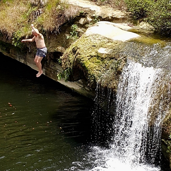 Christopher Baker leaps into a Belizean river on his break from QuickBooks training.