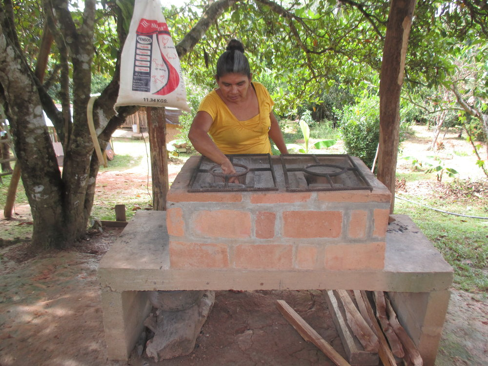 María Hernández inspects a new wood-conserving stove. - photo by Daysbeth López