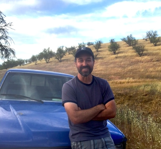 Nate Siemens on the Fat Uncle Farms ranch in Paso Robles with almond trees on the hillside