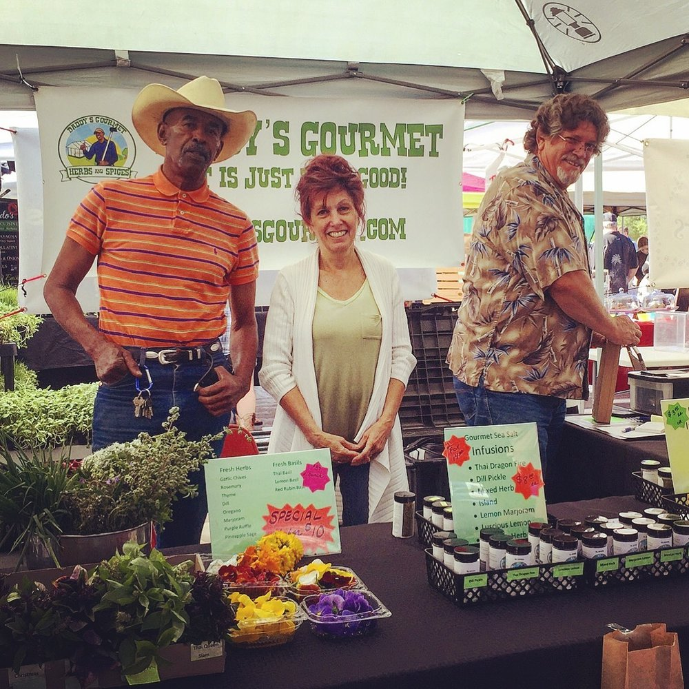 The Daddy's Gourmet team with fresh herbs from their organic farm and edible flowers. Shop and gift local on Treatmo.