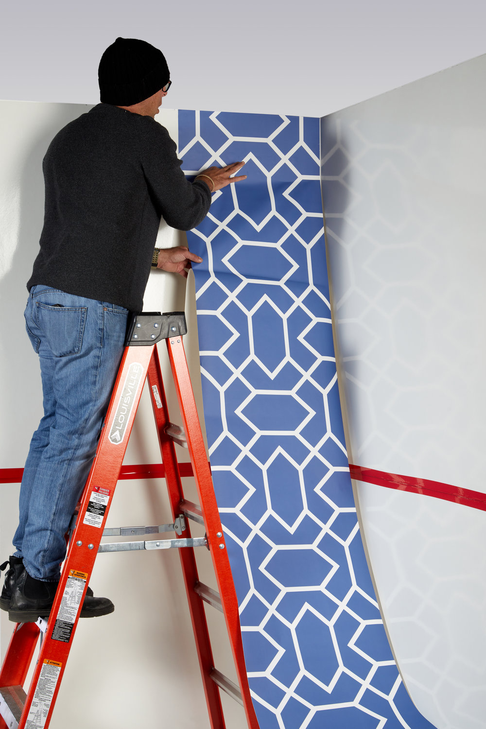 Installing a first section of adhesive backed wallpaper.