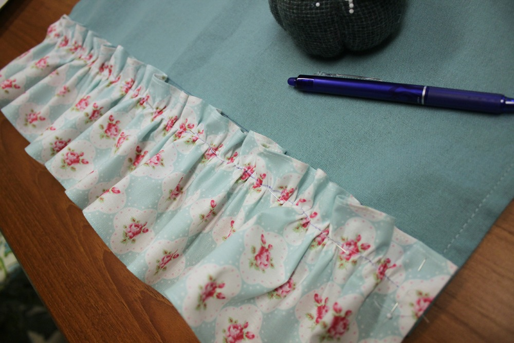 Attach the ruffle to the tea towel.