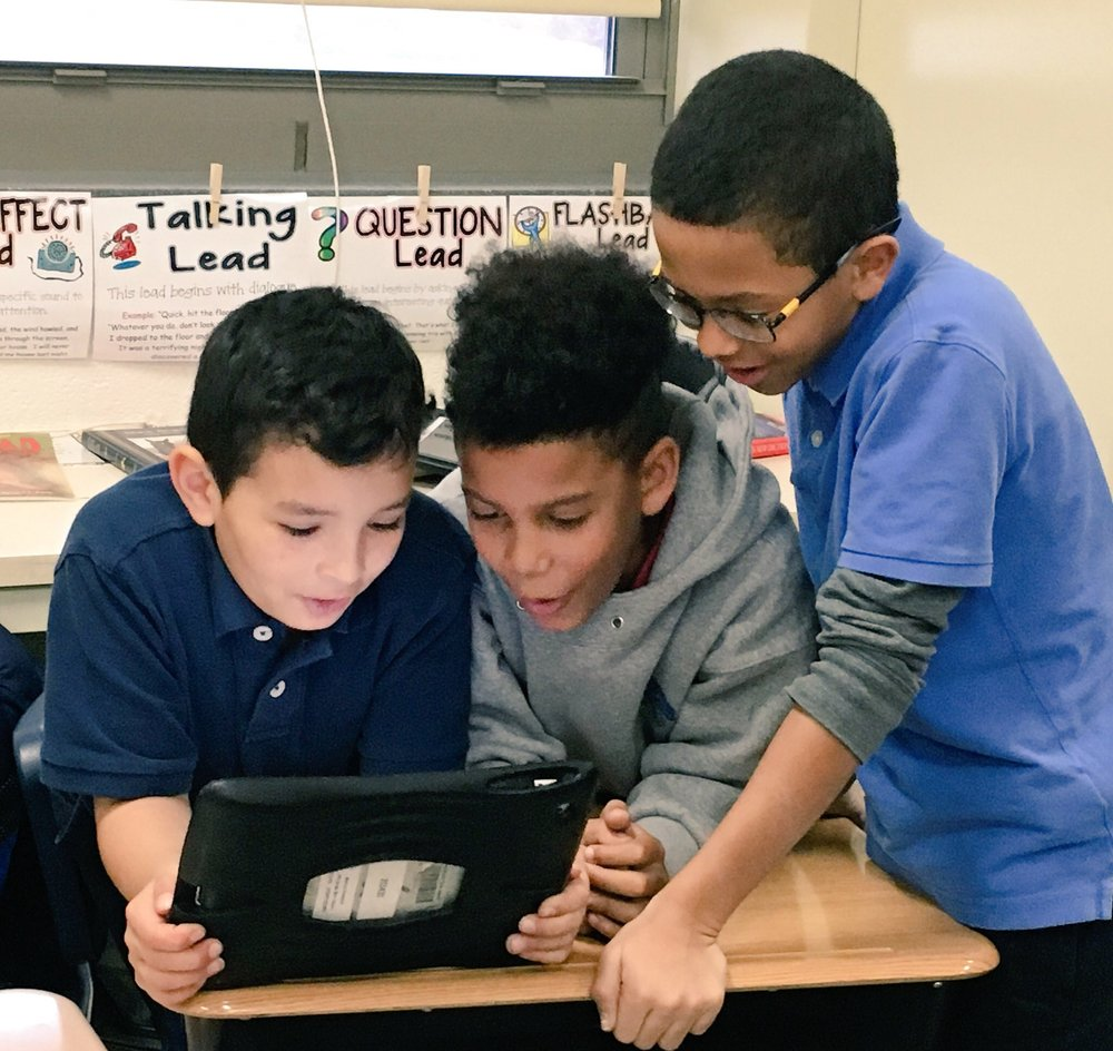 Three students at Sidener Academy work together on an Hour of Code activity.