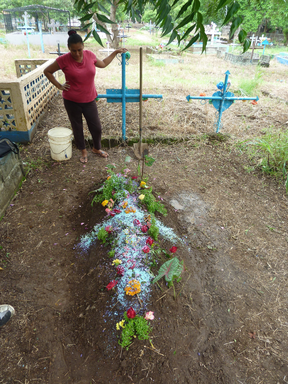 Dayani decora la tumba de su hijo Yader el día en que habría cumplido diecinueve años (2014). Foto de Douglas Haynes.