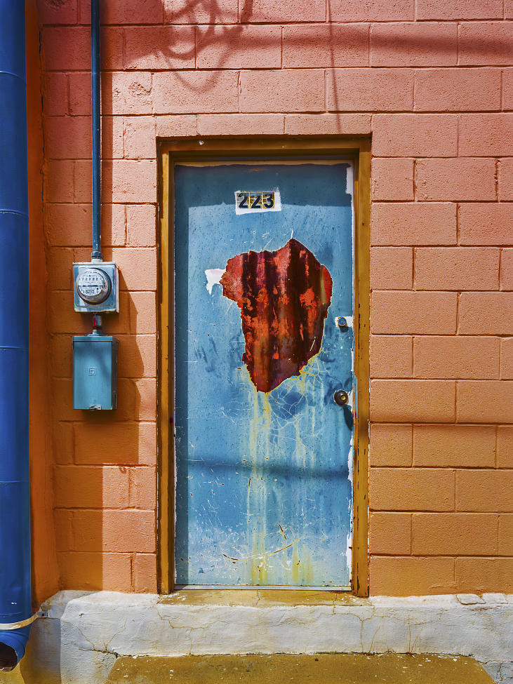 |#32| Steel Blue Painted cinder blocks, a salmon-tangerine smoothie. Splatters and rust bubbles leak and stain. Gas-meter pipping in, gutters pipping out.