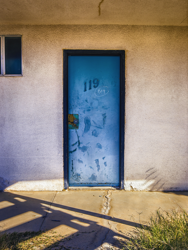 |#46| Air Superiority Blue Zigzag staircase throws piano-key shadows, an abandoned motel rusts under blasting sun rays. Encroaching weeds and fault lines, 119 slowly returns to the wild(blue yonder).