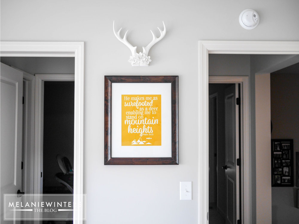 An inexpensive nursery printable topped with a more textured wall art provides a sophisticated look with a touch of whimsy.