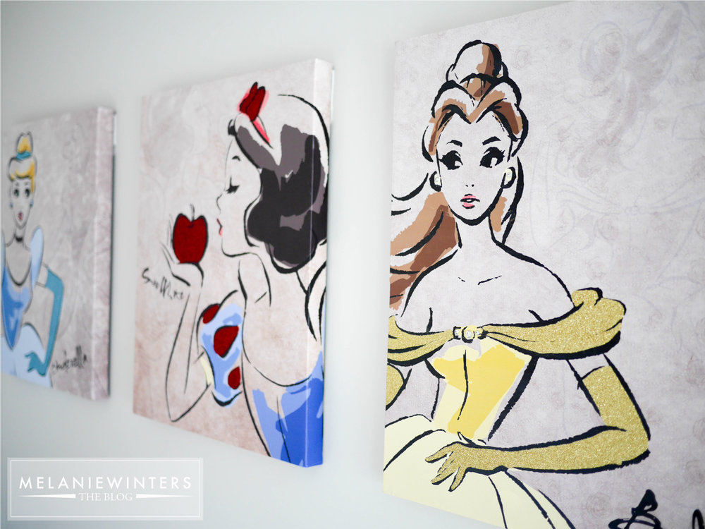 Disney princesses, yes. But with a tan background, retro/artsy vibe and subtle use of glitter these are far from the gaudy princess artwork usually associated with baby girl nurseries.