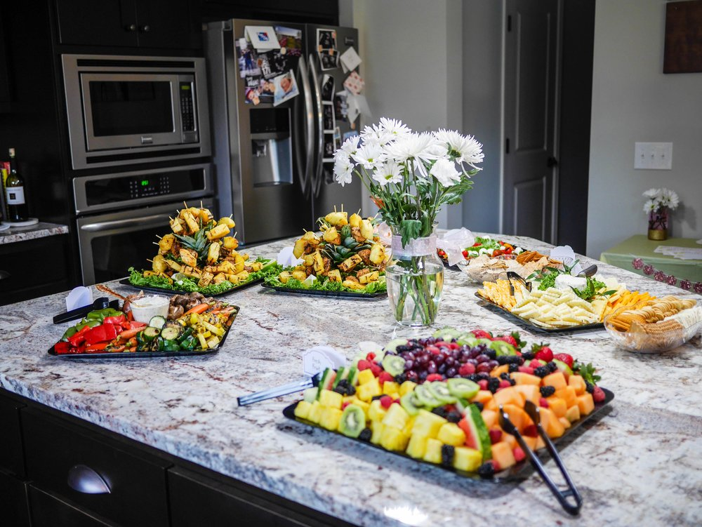 Fresh fruit, meats, cheeses, crackers, cold roasted vegetables and dip, grilled pineapple chicken skewers, and caprese skewers provide a well rounded spread for mama-to-be and friends.