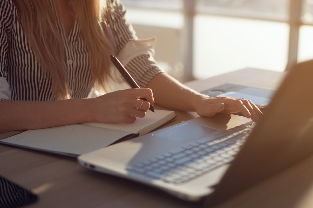 Woman freelancer female hands with pen writing on notebook at home or office