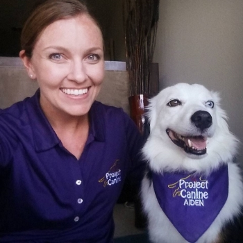Certified Project Canine team Andrea and Aiden wearing Project Canine logo gear.  Aiden is a herding dog mix.