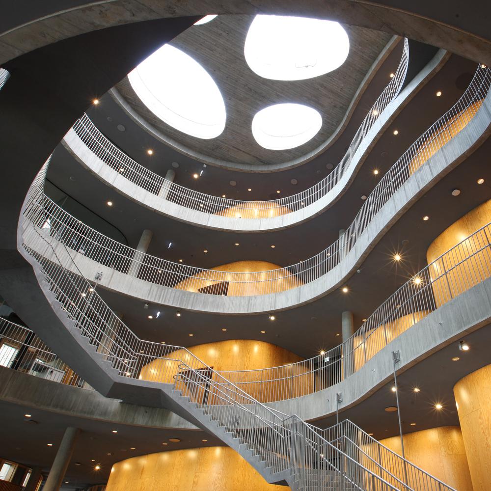 """Copenhagen plant science centre recieves prize from the munipality of frederiksberg """"... Et smukt atrium forener alle brugere af bygningen omkring sig, og den svungne betontrappe snor sig, som en DNA-streng op gennem rummet og tilbyder en flot rejse op mod de, ligeledes organisk formede, ovenlys i taget. Fra de øvre etager har man et flot kig ned over gulvet, som er udsmykket af billedkunstneren Milena Bonifacini. Samlet set danner den nye bygning en enestående smuk ramme omkring de nye faciliteter og er overalt forbilledligt gennemarbejdet, både i helheden og i detaljen."""" October 2017"""