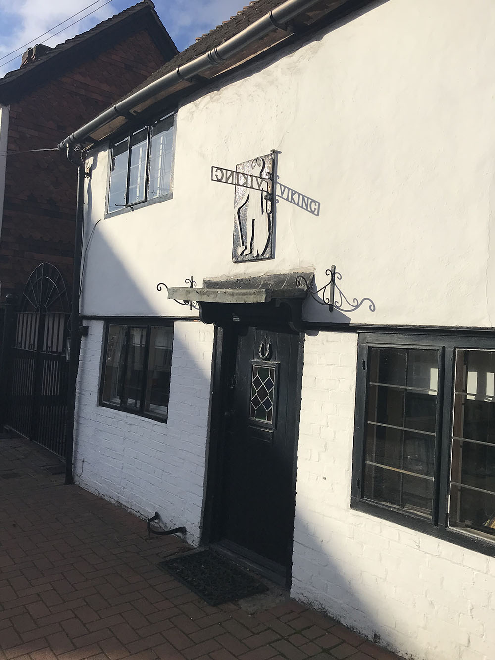5 - The sun casting a shadow on the sign of Viking Cottage, High Street.