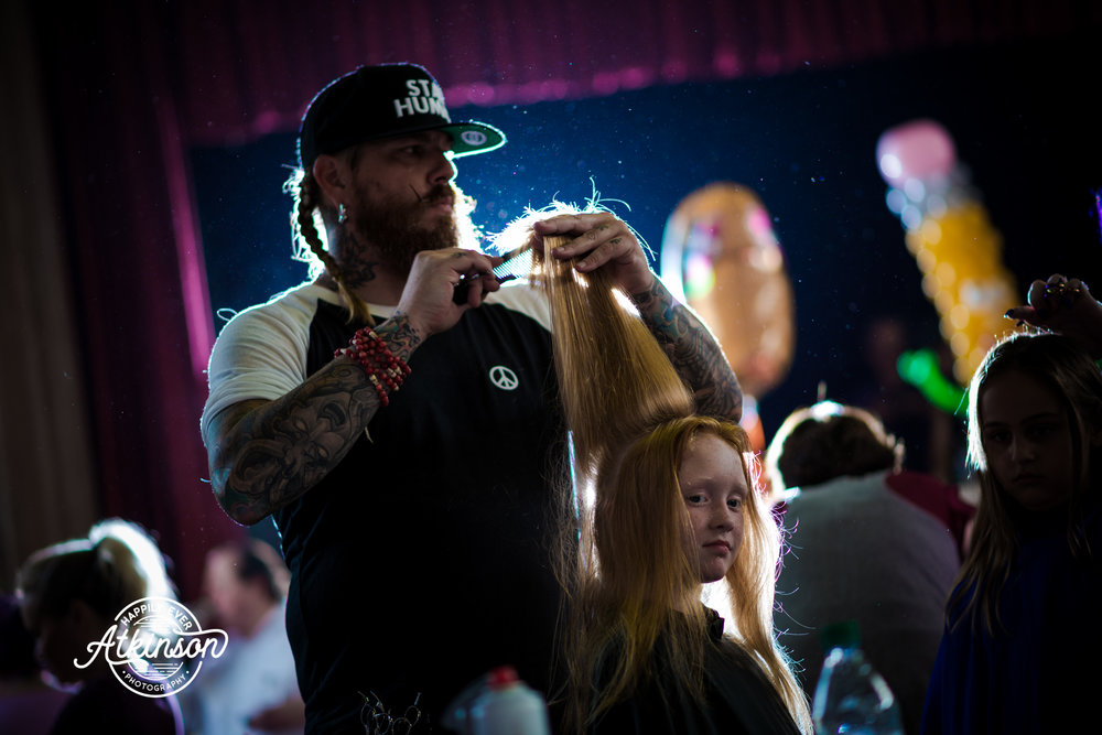 Gentleman cuts a little girl's hair
