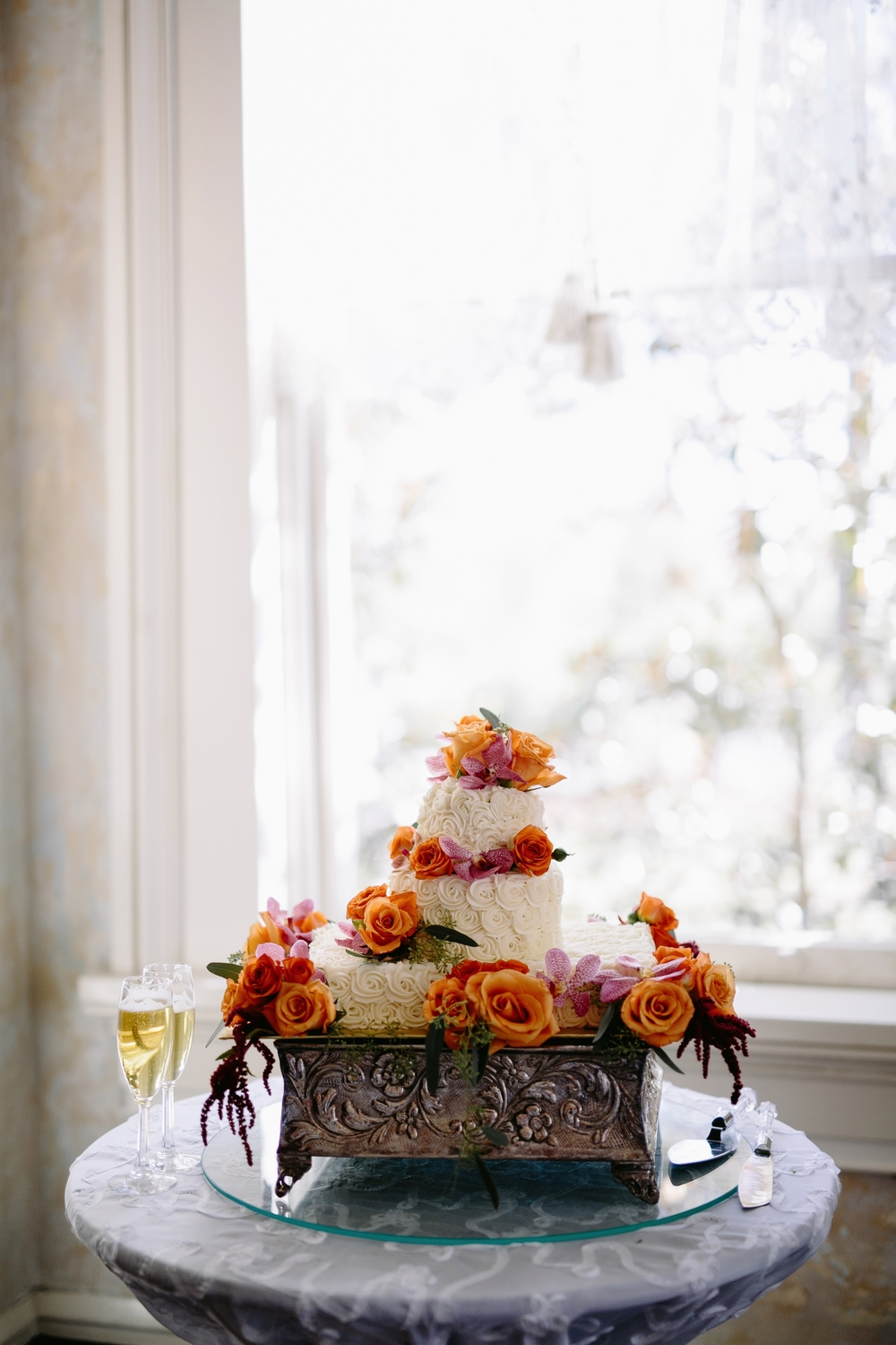 Add seasonal vibrant florals around each cake tier to add pops of color.  The popular rosette texture creates both dimension and an elegant romantic look.     Photo:  Q Avenue Photo