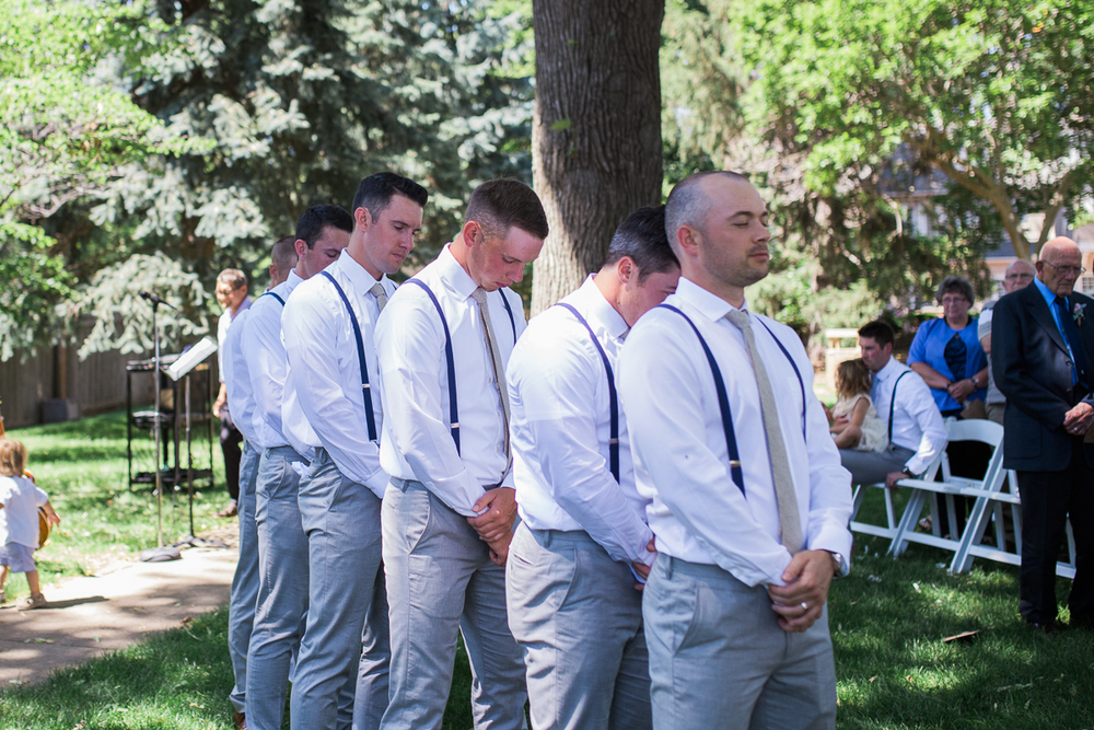 groomsmen in grey pants and suspenders