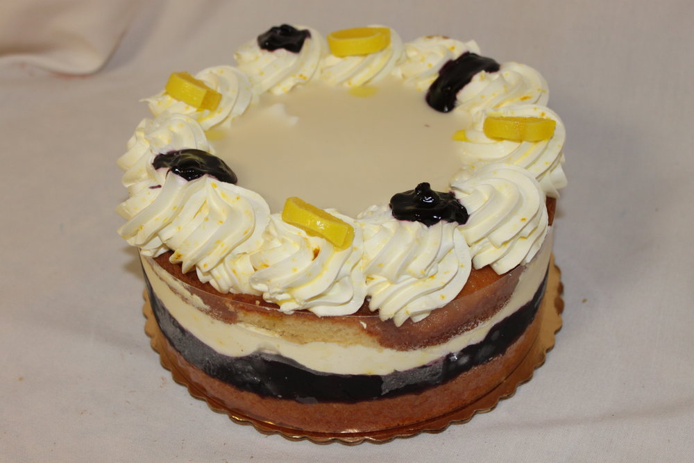 Gold cake layered with lemon mousse and fresh blueberries topped white ganache and Italian cream.
