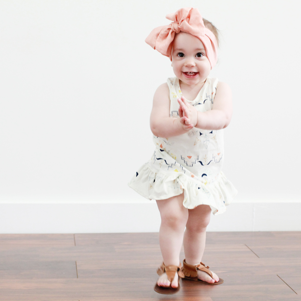 Zuzu's dress is by Little Shenanigan, her mocc sandals are by Harper and Paisley and her headwrap is by Little People Rocx.