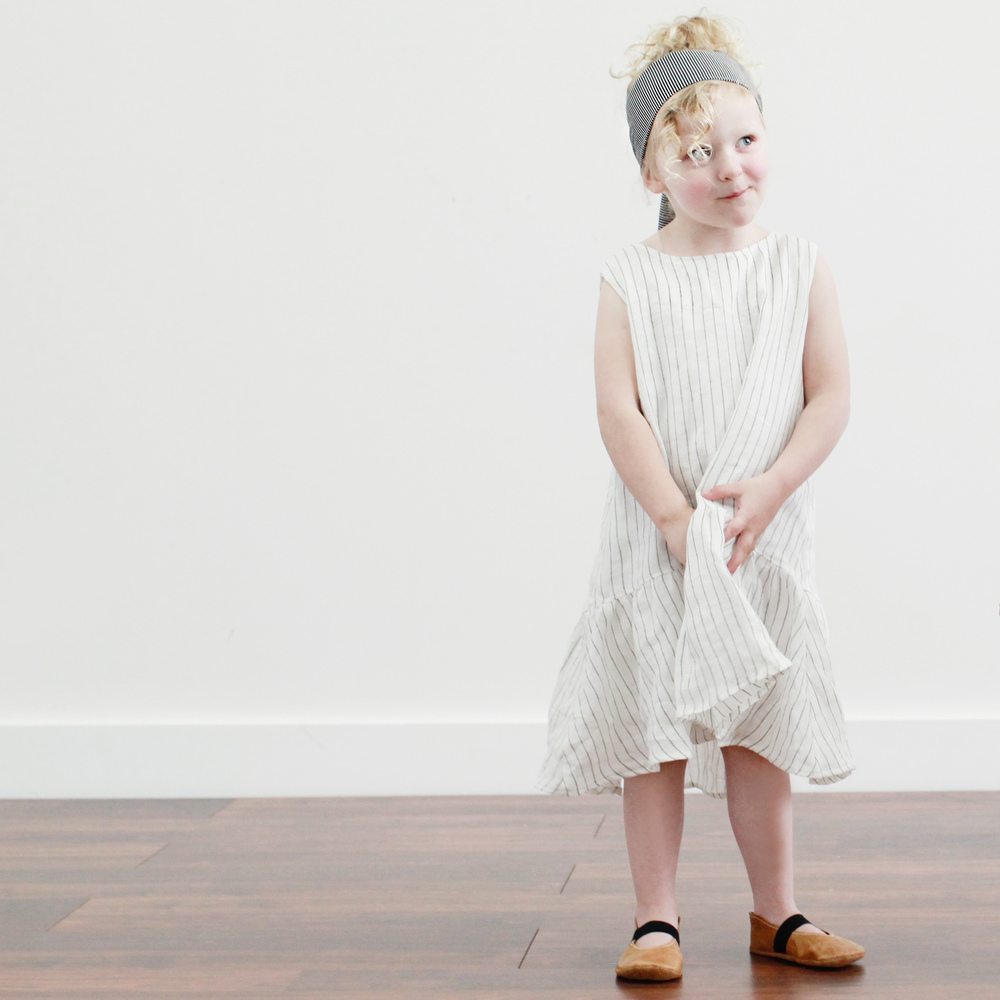 Charlie's dress is by LIttle Shenanigan. Her headwrap is by Little People Rocx and her flats are by Ullaviggo