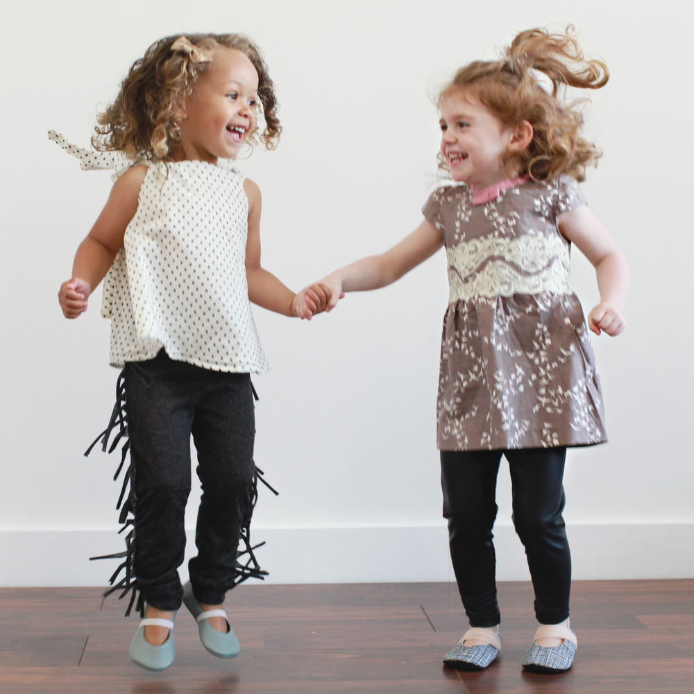 Fringe pants and bird dress by Spath Designs. Model on the left has Mina Loves Bows bow, Femke Clothing swing top, and gray Feather and Filly flats. Model on the right has Mina Loves Bows bow, leather pants by Half Pint Kids and shoes by Nori Child.