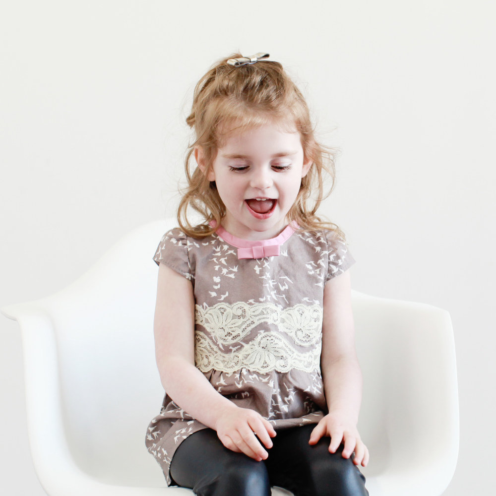 Harper is wearing a bird dress by Spath Designs. Faux leather pants by Half Pint Kids and bow by Mina Loves Bows.