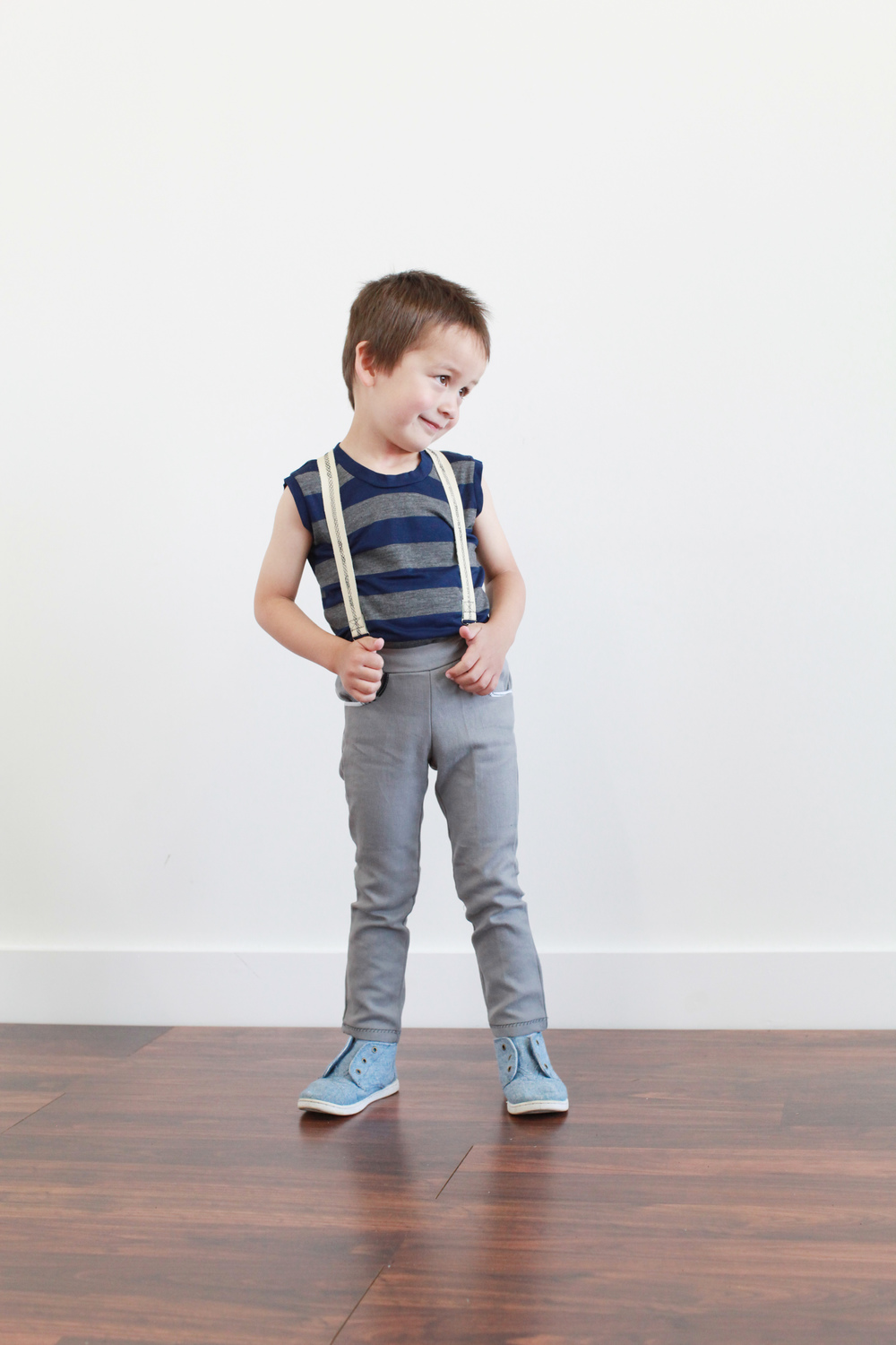 Lucan is wearing gray pants by Spath Designs. His tank and suspenders are by EW McCall and shoes are Toms.