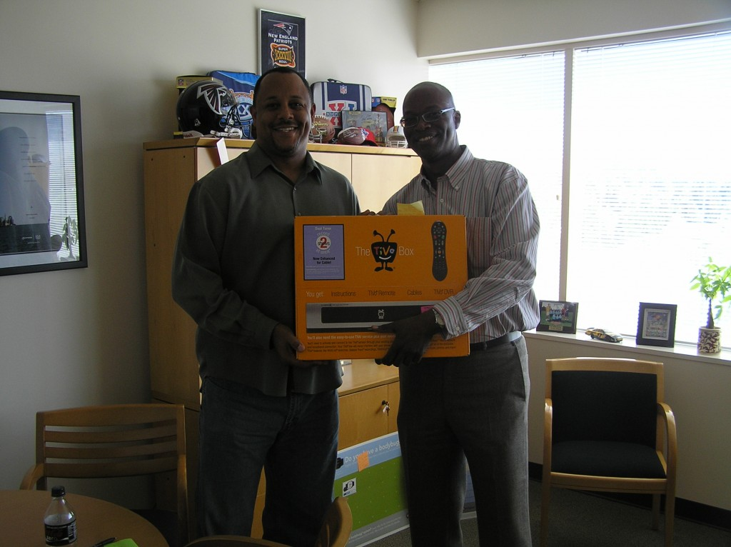 Tony Wells, (eft) CMO of 24-Hour Fitness, is presented with a free TiVo by Zuberance sales director Johnathan (JR) Robinson.